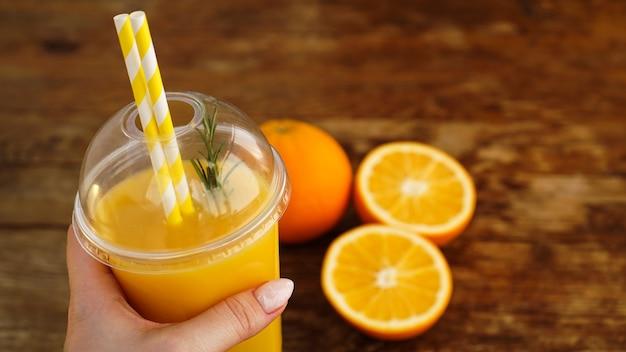 Dziewczyna ręka trzyma plastikowe szkło z sokiem pomarańczowym, drewniane tło z plastrami pomarańczy