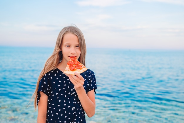 Dziewczyna relaks na plaży z kawałkiem pizzy w dłoni