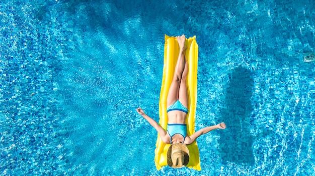 Dziewczyna relaks w basenie, dziecko pływa na nadmuchiwanym materacu i dobrze się bawi w wodzie na rodzinne wakacje, tropikalny ośrodek wypoczynkowy, widok z lotu ptaka z drona