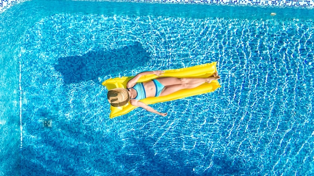 Dziewczyna relaksująca się w basenie, dziecko pływa na nadmuchiwanym materacu i bawi się w wodzie na rodzinnych wakacjach, tropikalny kurort, widok z lotu ptaka z drona