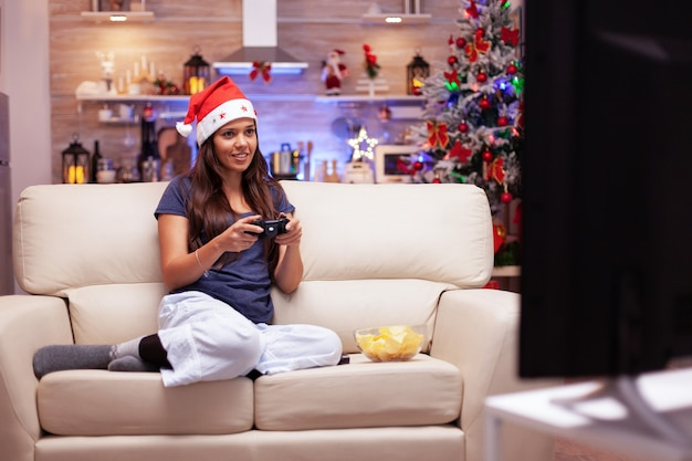Dziewczyna relaksuje się na kanapie w świątecznej udekorowanej kuchni, grając w gry wideo online