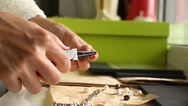 Dziewczyna robi biżuterię rękami.