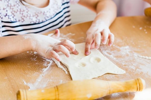 Dziewczyna robi ciasto na ciasto, wałek do ciasta, mąkę, pieczenie, gotowanie z ciasta i mąki