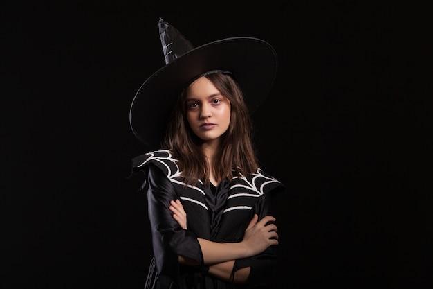 Dziewczyna robi ciemne zaklęcia ze skrzyżowanymi rękami i poważnym wyrazem twarzy na karnawał w halloween. młoda czarownica robi ciemne czary.