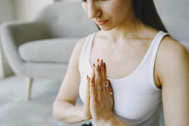 Dziewczyna robi ćwiczenia jogi w domu w pobliżu sofy i okna w odzieży sportowej