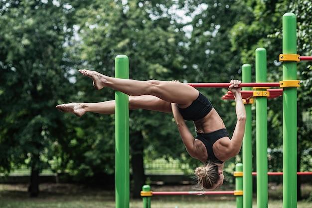Dziewczyna robi ćwiczenia na drążku.