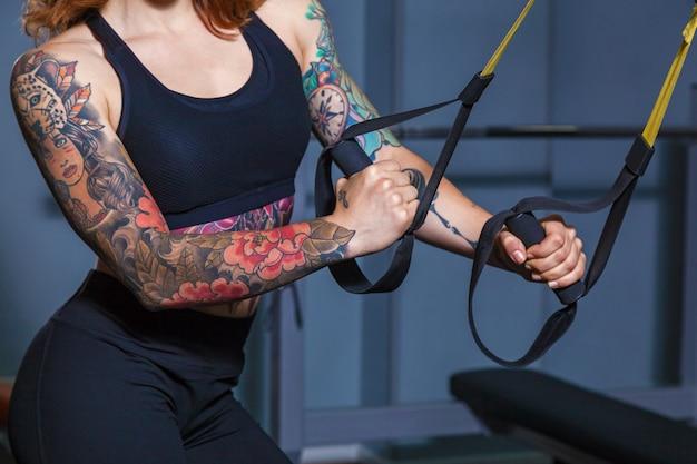 Dziewczyna robi ćwiczenia na pętlach sportowych. dziewczyna z tatuażami na fitness pokazuje piękne ciało z mięśniami. różnorodny sprzęt sportowy i sprzęt fitness do uprawiania sportu i fitness and