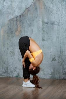 Dziewczyna robi ćwiczenia rozciągające plecy, nogi i pośladki.