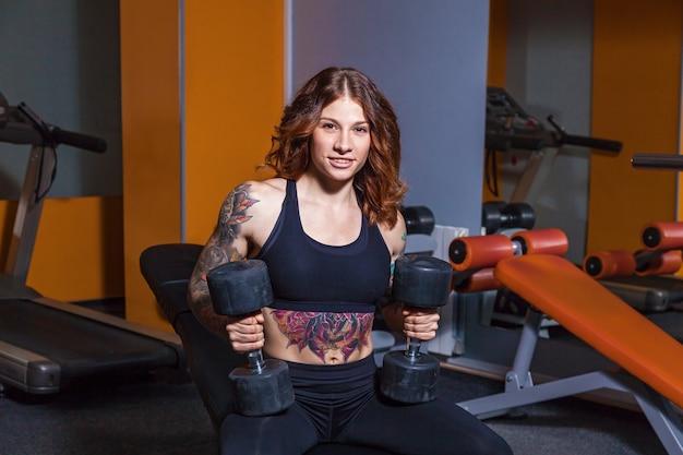 Dziewczyna robi ćwiczenia z hantlamidziewczyna z tatuażami na fitness pokazuje piękne ciało