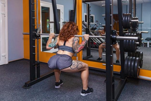 Dziewczyna robi ćwiczenia ze sztangą dziewczyna z tatuażami na fitness pokazuje piękne ciało