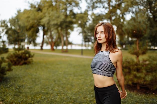 Dziewczyna robi fitness w parku o zachodzie słońca.