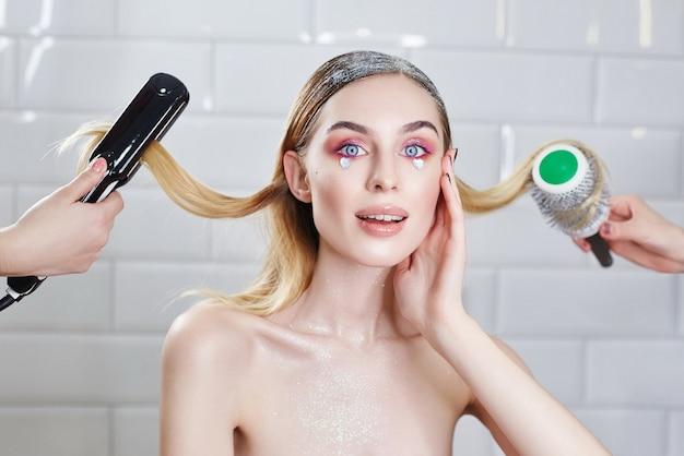 Dziewczyna robi fryzurę w salonie kosmetycznym, układanie włosów i czesanie. kobieta z jasnym błyszczącym kreatywnym makijażem w salonie kosmetycznym, pielęgnacja włosów