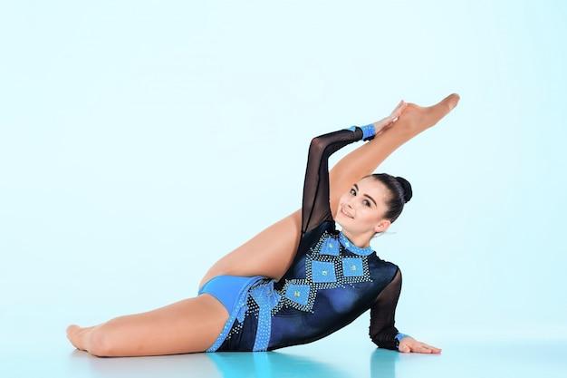 Dziewczyna robi gimnastyka tańczyć na niebieskim tle