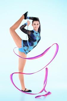 Dziewczyna robi gimnastyka tańczyć z kolorową wstążką na niebieskiej ścianie