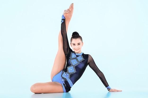 Dziewczyna robi gimnastyka taniec na niebieskiej ścianie