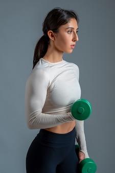 Dziewczyna robi hantle biceps na szarej ścianie