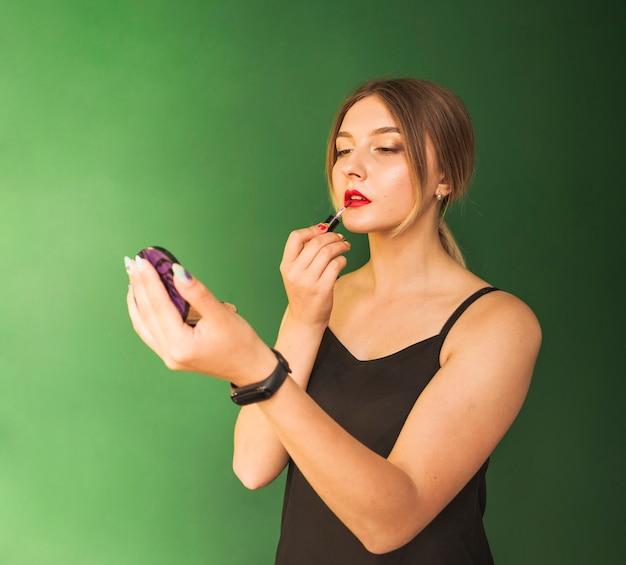 Dziewczyna robi jej makijaż w zielonym pokoju