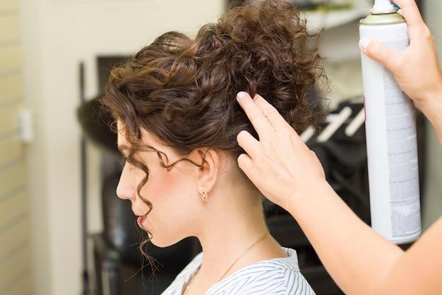 Dziewczyna robi jej włosy w salonie piękności
