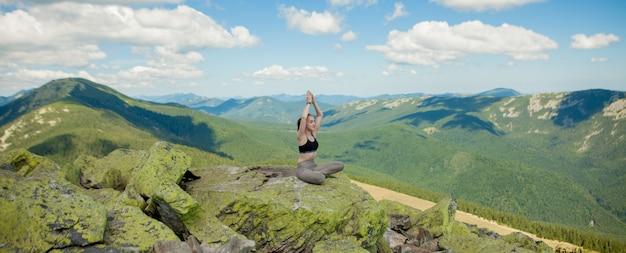 Dziewczyna robi joga ćwiczenia lotosu na szczycie góry.