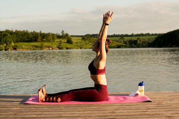 Dziewczyna robi joga na brzegu rzeki. utrzymuje proste plecy