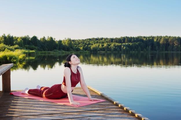 Dziewczyna robi joga na drewnianym molo nad jeziorem w lecie