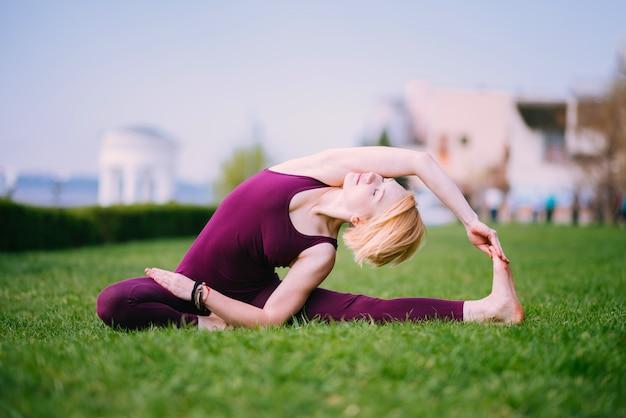 Dziewczyna robi joga na zielonej trawie na słonecznym dniu