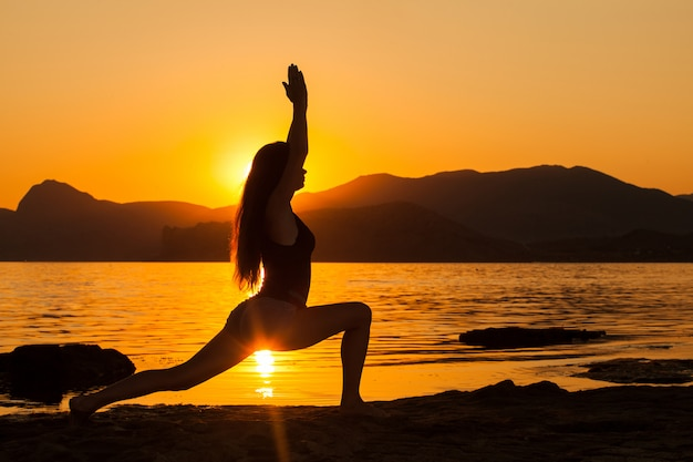 Dziewczyna robi joga nad oceanem.