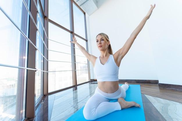Dziewczyna robi joga siedząc w pozie gołębia z podniesionymi rękami