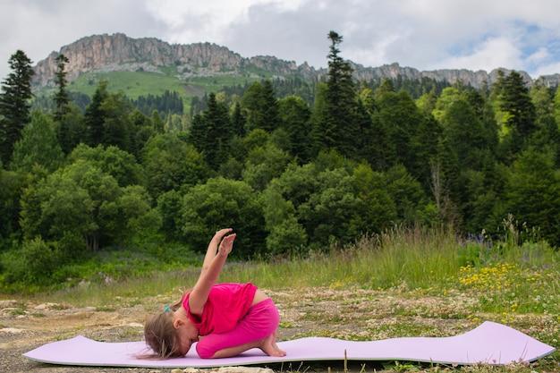 Dziewczyna robi joga w przyrodzie na tle gór