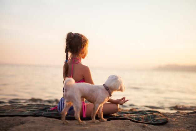 Dziewczyna robi joga z psem na zewnątrz natura o wschodzie słońca