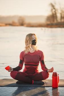 Dziewczyna robi jogę zimą na lodzie jeziora podczas zachodu słońca