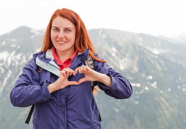 Dziewczyna robi kształt serca z górskiego krajobrazu. copyspace. młoda ładna rudowłosa kobieta stojąca w górach.