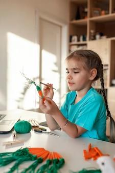 Dziewczyna robi marchewkę z drewnianymi szpilkami na ubrania na wielkanoc, patrząc online wideo na laptopie