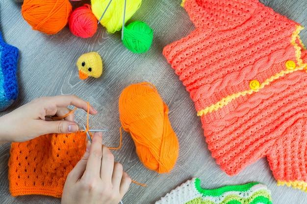 Dziewczyna robi na drutach igły dziewiarskie