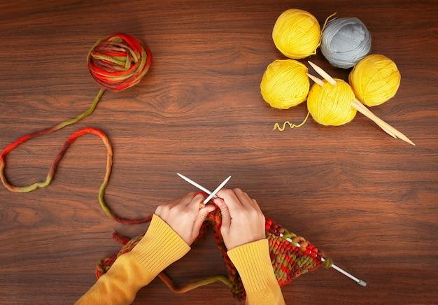 Dziewczyna robi na drutach na drutach, obok żółtych kulek przędzy