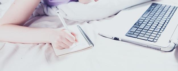 Dziewczyna robi notatki na zeszycie