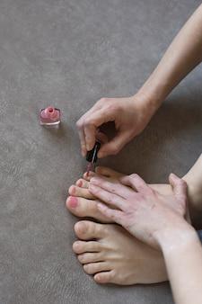 Dziewczyna robi pedicure w domu, orientacja pionowa. kobiece ręce malować paznokcie z różowym lakierem do paznokci, szczelnie-do góry