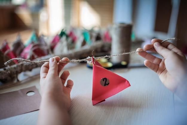 Dziewczyna robi ręcznie robiony kalendarz adwentowy z kolorowych trójkątów papieru