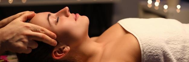 Dziewczyna robi relaksacyjny masaż głowy w gabinecie kosmetycznym
