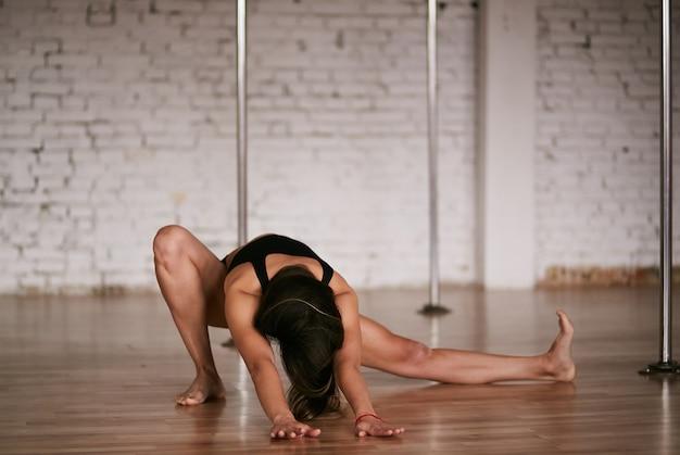 Dziewczyna robi rozciąganie jej pleców i nóg przed treningiem na siłowni na rurze tanecznym