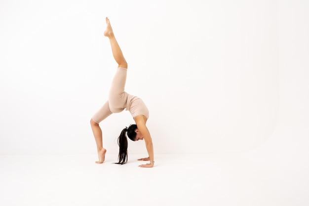 Dziewczyna robi rozciąganie w studio na białym tle. piękna gimnastyczka o elastycznym ciele i sportowym stroju.