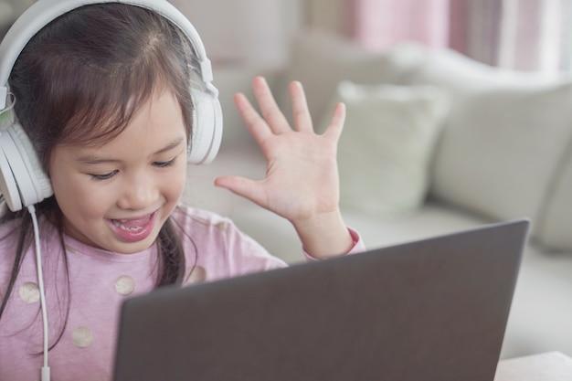 Dziewczyna robi rozmowy wideo facetime z laptopem w domu, nauczanie w domu, uczenie się zdalnie koncepcji