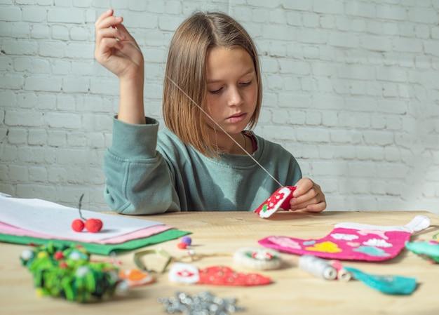 Dziewczyna robi świąteczne dekoracje z filcu, dziecko tworząc nowy rok wystrój filcu