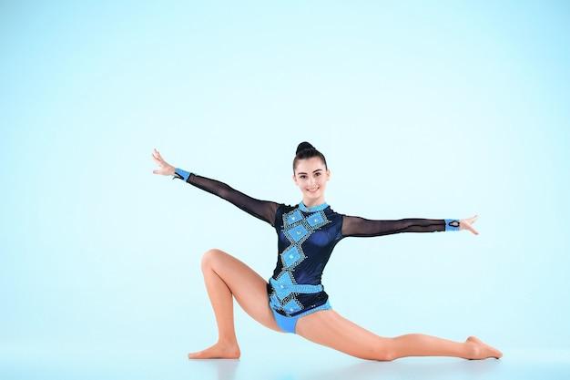 Dziewczyna robi taniec gimnastyka na niebieskiej przestrzeni