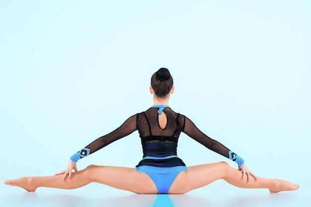 Dziewczyna robi taniec gimnastyka na niebieskim tle