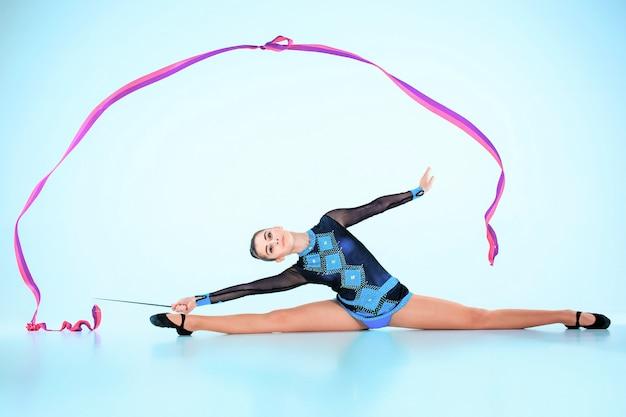 Dziewczyna robi taniec gimnastyki z kolorową wstążką na niebieskiej przestrzeni