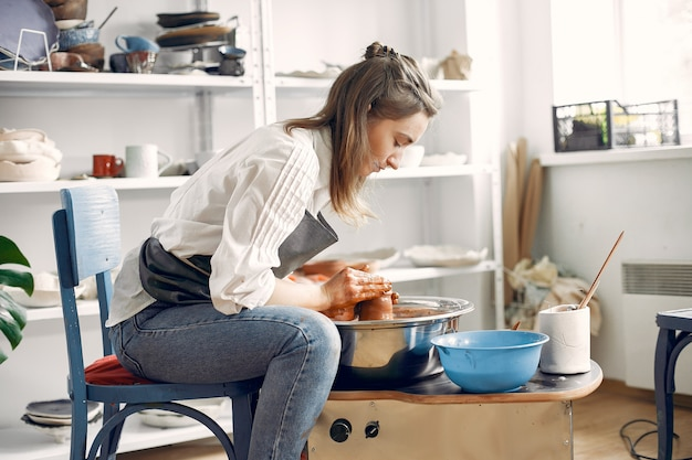 Dziewczyna robi vaze z gliny na maszynie garncarskiej