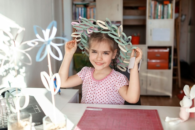 Dziewczyna robi wieniec z tubą na papier toaletowy podczas lekcji mistrzowskich online, obchody wielkanocne zero waste