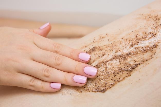 Dziewczyna robi zabiegi kosmetyczne w łazience. peeling do kawy do stóp