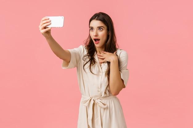 Dziewczyna robi zafascynowany i zaskoczony wyraz twarzy jako rozmowa z dziewczyną podczas rozmowy wideo przez telefon. urocza brunetka kobieta w sukience, robiąc selfie, z trudem łapiąc otwarte usta, stojąc różową ścianę